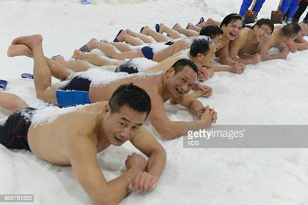 Ten winter swimming lovers lie down on snow with the local temperature of minus 6 degree celsius as they compete to see how long they can stay in the...