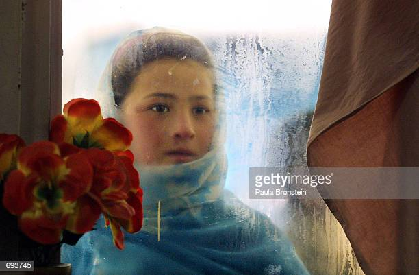 A ten year old girl named Switan looks into the window of the Herat restaurant January 13 2002 while begging for food in Kabul Afghanistan She gazes...