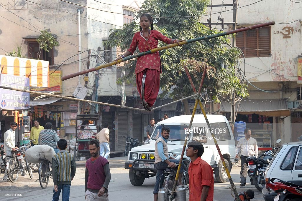 Ten year old Indian girl, Kajal performs a balancing act on a rope during a street show in Amritsar on November 19, 2014. Travelling Indian performers, who earn a meagre income from putting on shows on the streets, often scout areas to gather a large street audience who then give money on a collection plate at the end of the show.