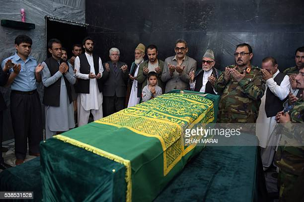 Ten yearold Mustafa son of Afghan reporter Zabihullah Tamannarelatives and friends pray around the coffin during a ceremony at a military hospital...
