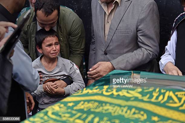 TOPSHOT Ten yearold Mustafa son of Afghan reporter Zabihullah Tamannarelatives and friends pray around the coffin during a ceremony at a military...