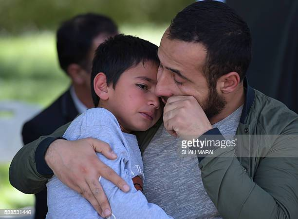 Ten yearold Mustafa son of Afghan reporter Zabihullah Tamanna mourns as he looks up at an uncle of Afghan reporter Zabihullah during a ceremony at a...