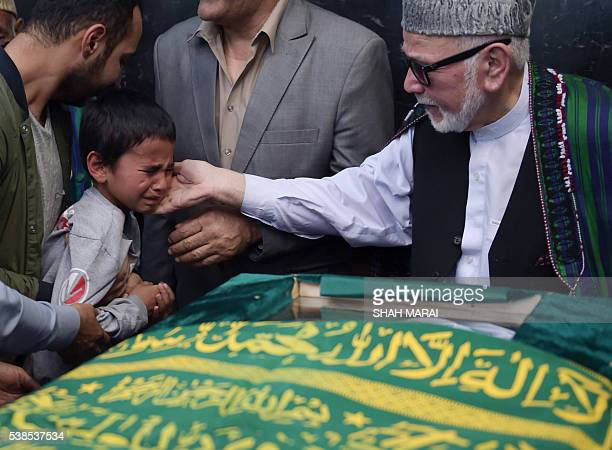Ten yearold Mustafa son of Afghan reporter Zabihullah Tamannais conforted during a ceremony at a military hospital in Kabul on June 7 2016 Zabihullah...