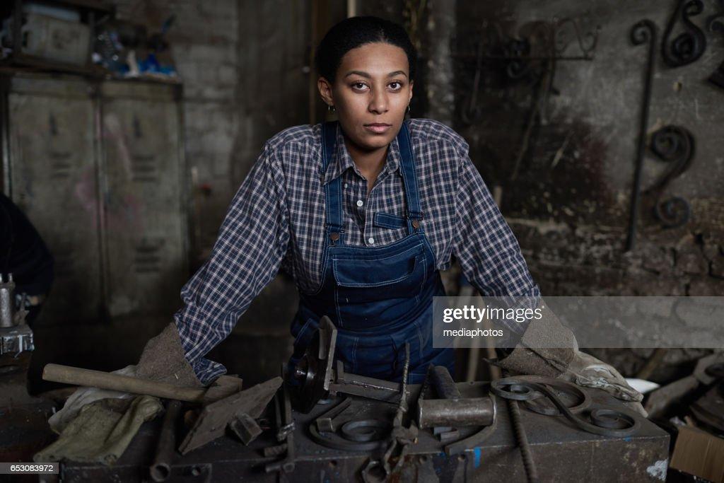 Tenacious female blacksmith : Stock Photo