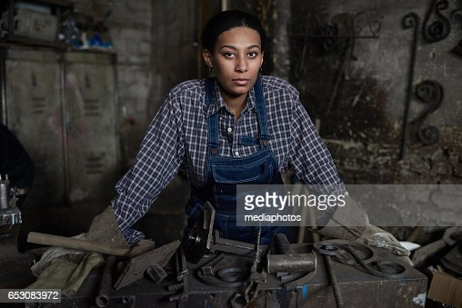 Tenacious female blacksmith : Stock Photo