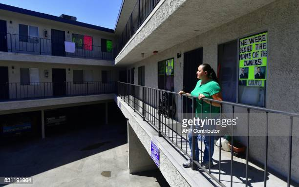 Tenant Maria Aguilar looks out from a balcony in front of her home on August 3 2017 in the Boyle Heights neighborhood of Los Angeles where with no...