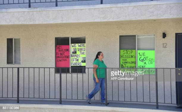 Tenant Maria Aguilar walks past posters in front of homes including hers on a balcony in this apartment block where with no rent control due to the...
