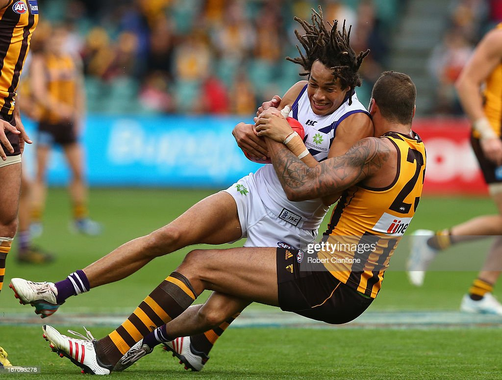 Tendai Mzungu of the Dockers is tackled by Lance Franklin of the Hawks during the round four AFL match between the Hawthorn Hawks and the Fremantle Dockers at Aurora Stadium on April 20, 2013 in Launceston, Australia.