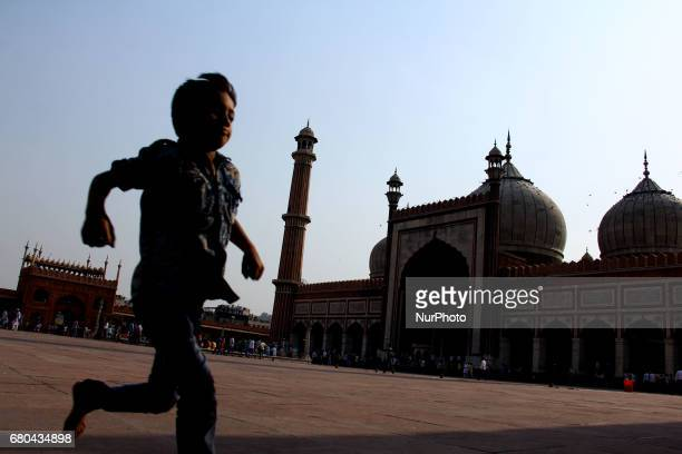 Tender aged boy is running away in a bid to avoid the heated floor inside the premises of Jamia Masjid here in Old Delhi on May 8 2017 as temperature...