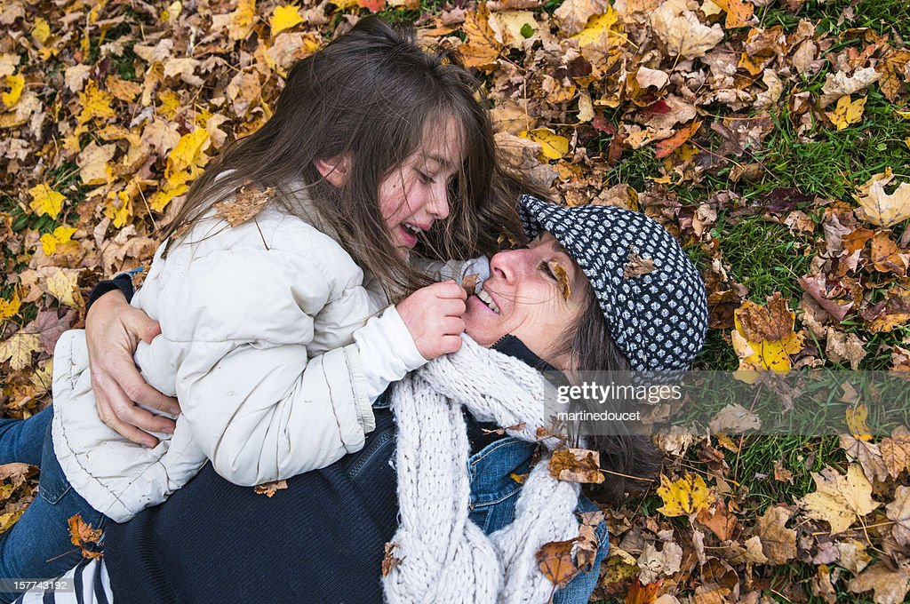 Tender moment between mother and daughter in autumn leaves. : Stock Photo