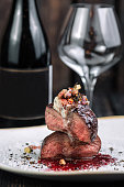 Tenderloin steak on irregular shape plate with wineglass and bottle of wine and wineglass on dark background