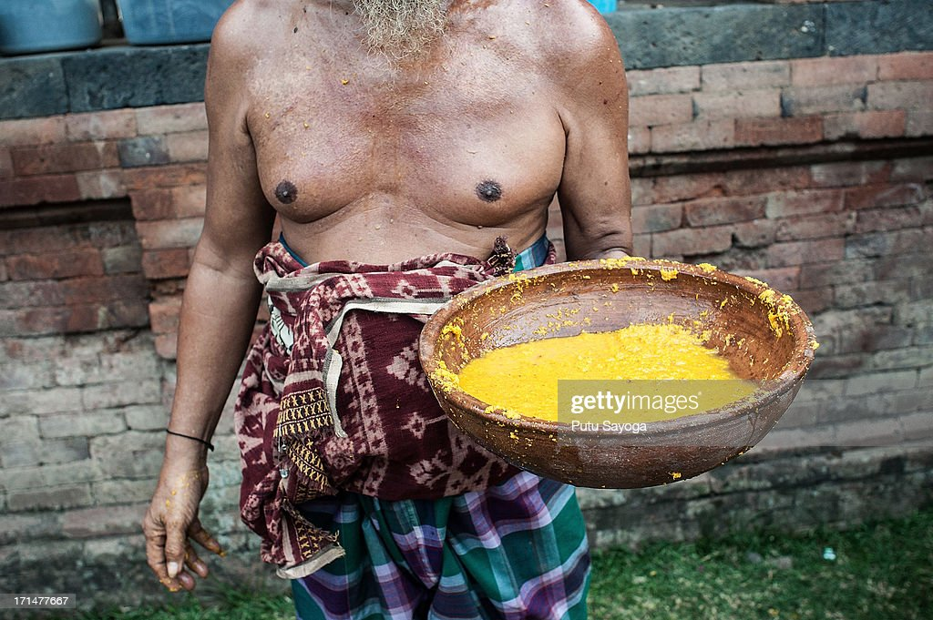 A Tenganananese man carries traditional potion made of turmeric and vinegar to heal the wounds of the fighters during the Pandanus War ritual on June 25, 2013 in Tenganan, Karangasem, Bali, Indonesia. Every year Tengananese people in the island of Bali celebrate a month-long ceremony called 'Usabha Sambah', to demonstrate respect to the God Indra, the Hindu god of war. One of the rituals during the ceremony is a Pandanus War or 'Mekare Kare', where two Tengananese men duel using thorny pandanus as their weapon.