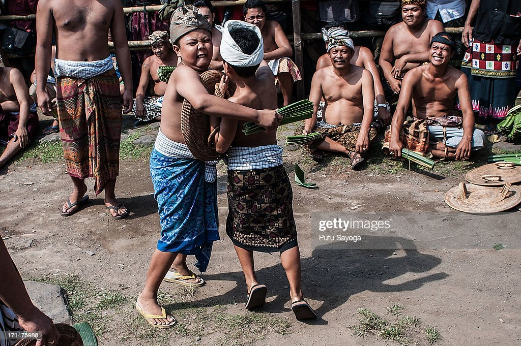 Tengananese children fight each other using thorny pandanus leaves during a pandanus war ritual on June 25, 2013 in Tenganan, Karangasem, Bali, Indonesia. Every year Tengananese people in the island of Bali celebrate a month-full ceremony called 'Usabha Sambah', to demonstrate respect to the God Indra, the Hindu god of war. One of the rituals during the ceremony is a Pandanus War or 'Mekare Kare', where two Tengananese men duel using thorny pandanus as their weapon.