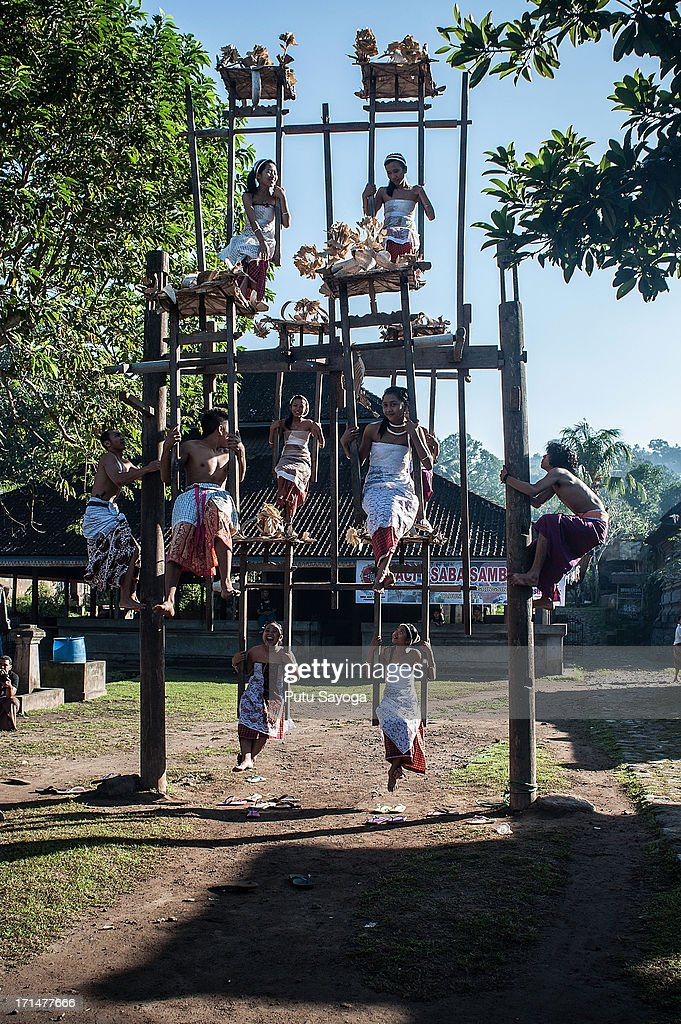 Tengananese girls play on a traditional ferris wheel before the Pandanus War ritual begins on June 25, 2013 in Tenganan, Karangasem, Bali, Indonesia. Every year Tengananese people in the island of Bali celebrate a month-long ceremony called 'Usabha Sambah', to demonstrate respect to the God Indra, the Hindu god of war. One of the rituals during the ceremony is a Pandanus War or 'Mekare Kare', where two Tengananese men duel using thorny pandanus as their weapon.