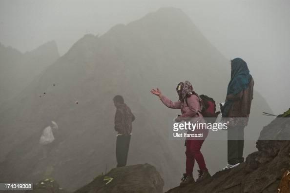 Tenggerese worshipper throws offering at crater of Mount Bromo during the Yadnya Kasada Festival at crater of Mount Bromo on July 24 2013 in...