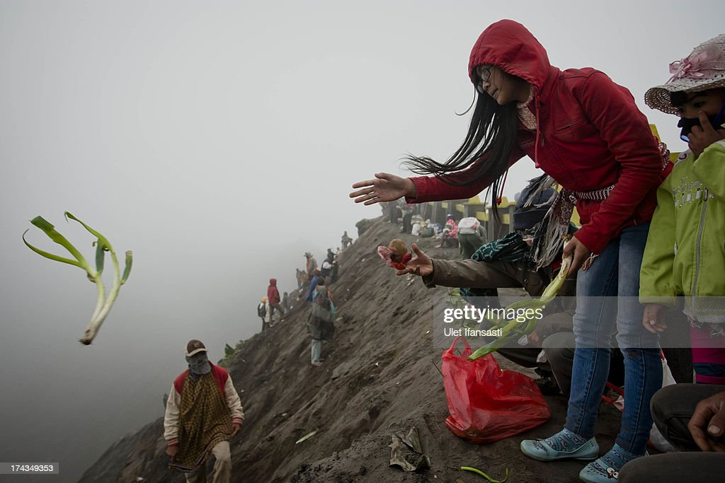 Tenggerese worshipper throws vegetables for an offering of Mount Bromo during the Yadnya Kasada Festival at crater of Mount Bromo on July 24, 2013 in Probolinggo, East Java, Indonesia. The festival is the main festival of the Tenggerese people and lasts about a month. On the fourteenth day, the Tenggerese make the journey to Mount Bromo to make offerings of rice, fruits, vegetables, flowers and livestock to the mountain gods by throwing them into the volcano's caldera. The origin of the festival lies in the 15th century when a princess named Roro Anteng started the principality of Tengger with her husband Joko Seger, and the childless couple asked the mountain Gods for help in bearing children. The legend says the Gods granted them 24 children but on the provision that the 25th must be tossed into the volcano in sacrifice. The 25th child, Kesuma, was finally sacrificed in this way after initial refusal, and the tradition of throwing sacrifices into the caldera to appease the mountain Gods continues today.