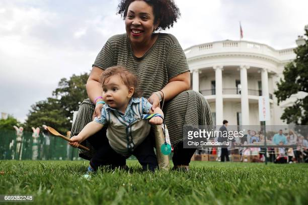 Tenmonthold Joseph Montgomery David Rosner and his mother Leslie Greene of Centreville VA roll a colored egg down the White House South Lawn during...