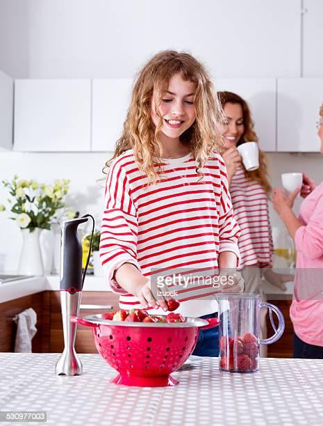 Tennager fille prepering jus de fruits smoothie à la fraise