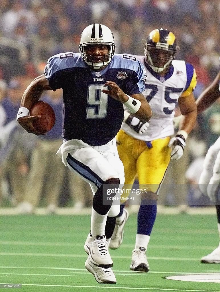 Tennessee Titans quarterback Steve McNair takes off on a run as the St Louis Rams defensive tackle D'Marco Farr persues during second half action in...