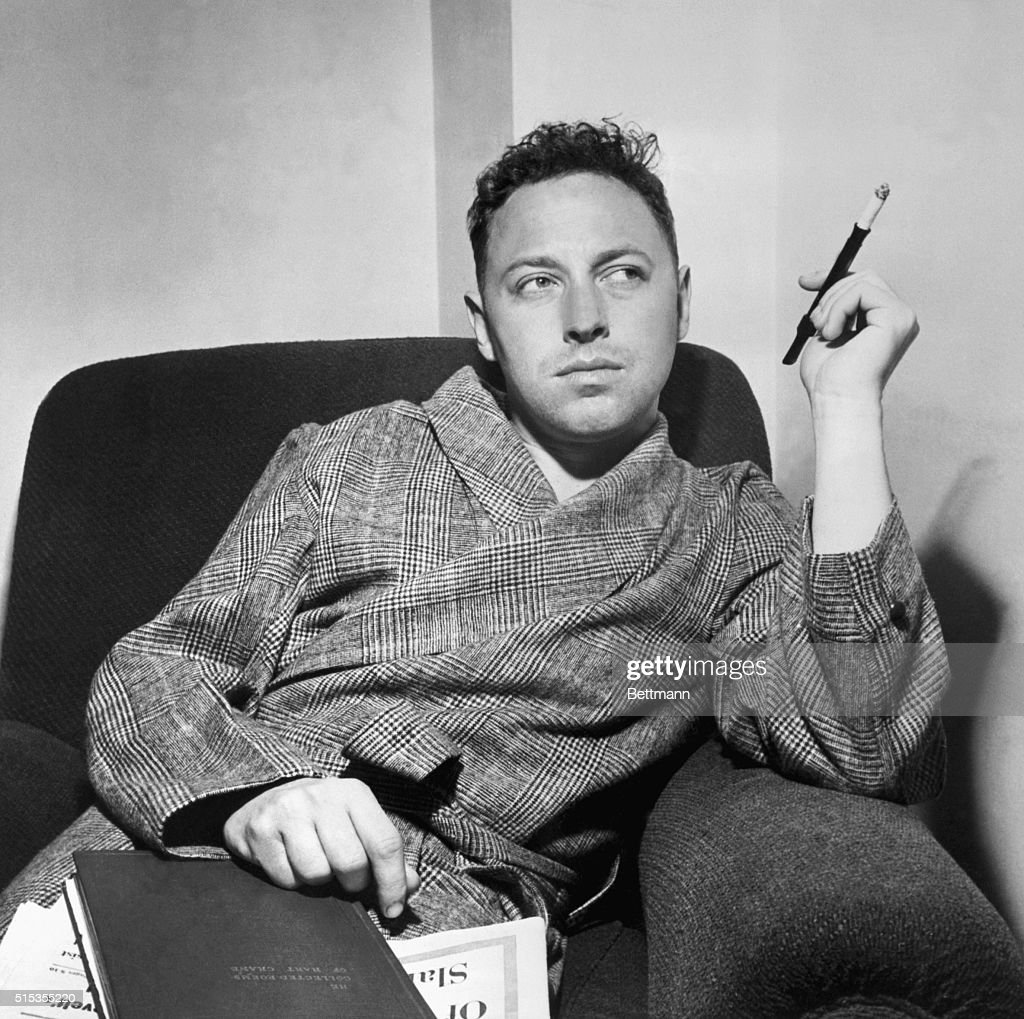 Tennessee Williams, famous author and playwright, seated in a chair smoking a cigarette. Undated photograph.