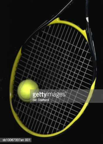 Tennis ball and racket on black background