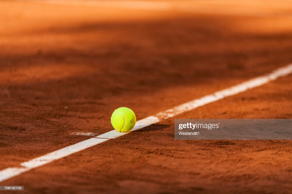 Tennis ball hitting the line on clay court : Photo