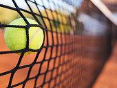 Tennis net stop a shot on a clay court.