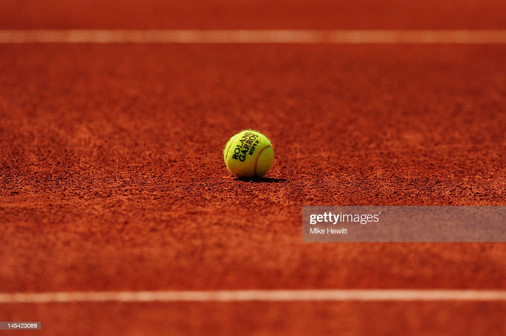 A tennis ball marked with 'Roland Garros 2012' rests on the clay during day three of the French Open at Roland Garros on May 29 2012 in Paris France