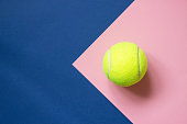 Tennis ball on blue and pink paper background. Concept sport. Copy space