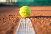 Small tennis ball lying on white line on tennis court on sunny day.