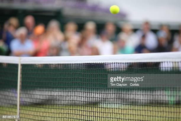 A tennis ball passes over the net on the outer courts during the Wimbledon Lawn Tennis Championships at the All England Lawn Tennis and Croquet Club...