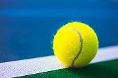 A stock photo of a Tennis ball on the lines of a Tennis Court