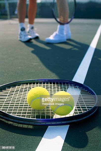 Tennis balls and racquet on court with people