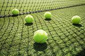 Five tennis balls on the court grass