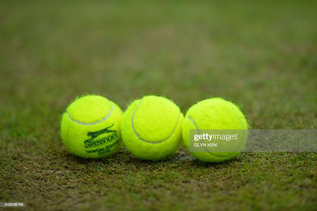Tennis balls sit on a court on the third day of the 2016 Wimbledon Championships at The All England Lawn Tennis Club in Wimbledon, southwest London, on June 29, 2016. / AFP / GLYN KIRK / RESTRICTED TO EDITORIAL USE / The erroneous mention[s] appearing in the metadata of this photo by GLYN KIRK has been modified in AFP systems in the following manner: [Petkovic won] instead of [Hibino won]. Please immediately remove the erroneous mention[s] from all your online services and delete it (them) from your servers. If you have been authorized by AFP to distribute it (them) to third parties, please ensure that the same actions are carried out by them. Failure to promptly comply with these instructions will entail liability on your part for any continued or post notification usage. Therefore we thank you very much for all your attention and prompt action. We are sorry for the inconvenience this notification may cause and remain at your disposal for any further information you may require.