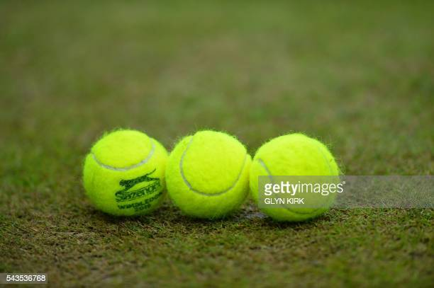 Tennis balls sit on a court on the third day of the 2016 Wimbledon Championships at The All England Lawn Tennis Club in Wimbledon southwest London on...