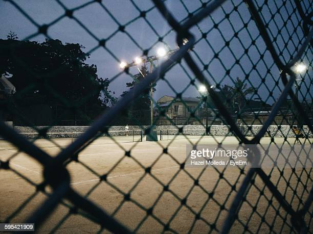 Tennis Court Seen From Chainlink Fence Against Sky At Night