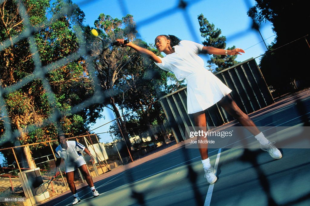 Tennis, doubles match, woman playing forehand return by net : Stock Photo