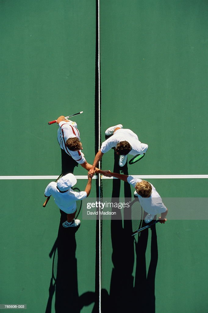 Tennis, doubles players shaking hands over net, overhead view : Stock Photo