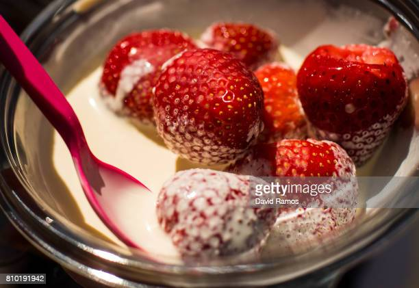 A tennis fan eats strawberries and cream on day five of the Wimbledon Lawn Tennis Championships at the All England Lawn Tennis and Croquet Club on...