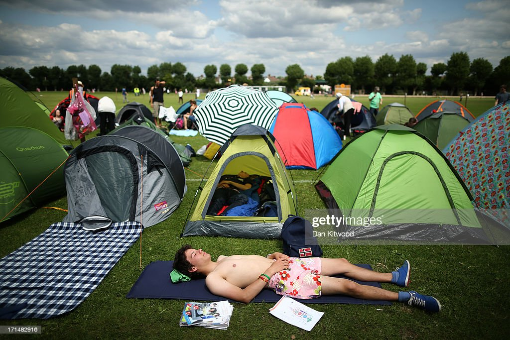 A tennis fan relaxes in the sun outside his tent during day two of the Wimbledon Lawn Tennis Championships at the All England Lawn Tennis and Croquet Club on June 25, 2013 in London, England.