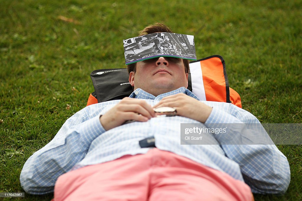 A tennis fan takes a nap in the queue outside the All England Lawn Tennis and Croquet Club on Day One of the Wimbledon Lawn Tennis Championships at...
