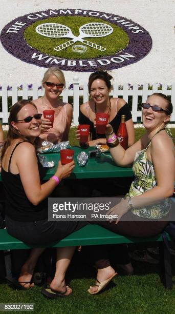 Tennis fans enjoy a drink on Henman Hill before play starts on the fifth day of The All England Lawn Tennis Championships at Wimbledon
