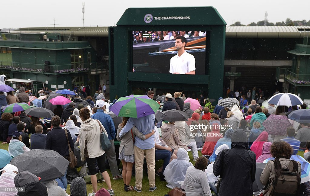 Tennis fans shelter from the rain as they watch a giant television screen showing the game between Serbia's Novak Djokovic and Bobby Reynolds of US during the second round of the men's singles on day four of the 2013 Wimbledon Championships tennis tournament at the All England Club in Wimbledon, southwest London, on June 27, 2013.