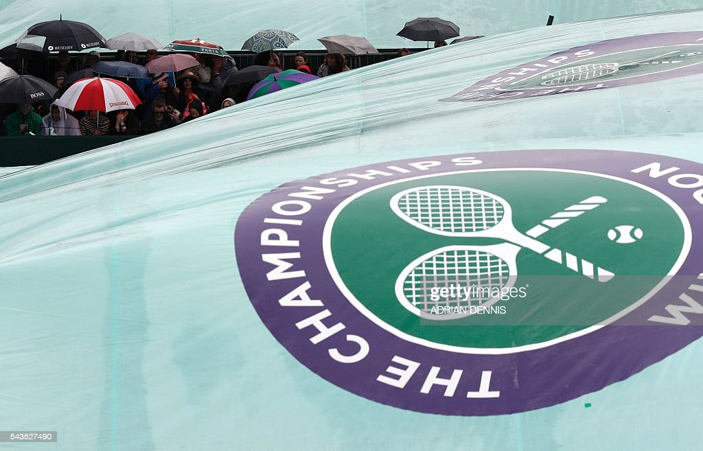 Tennis fans stand under umbrellas as rain halts the start of the third day of the 2016 Wimbledon Championships at The All England Lawn Tennis Club in Wimbledon, southwest London, on June 29, 2016. / AFP / ADRIAN
