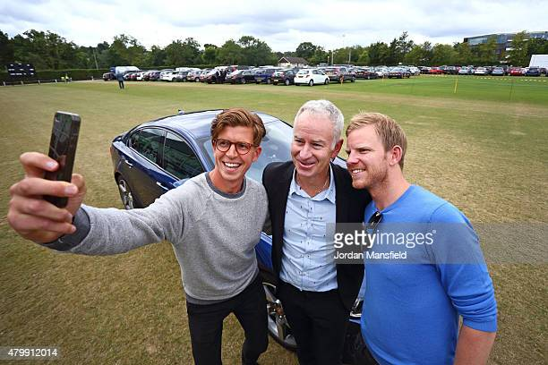 Tennis fans Tom Payne and Nick Webb pose for a picture with 3time Wimbledon Champion John McEnroe in front of the Jaguar XE as part of the...