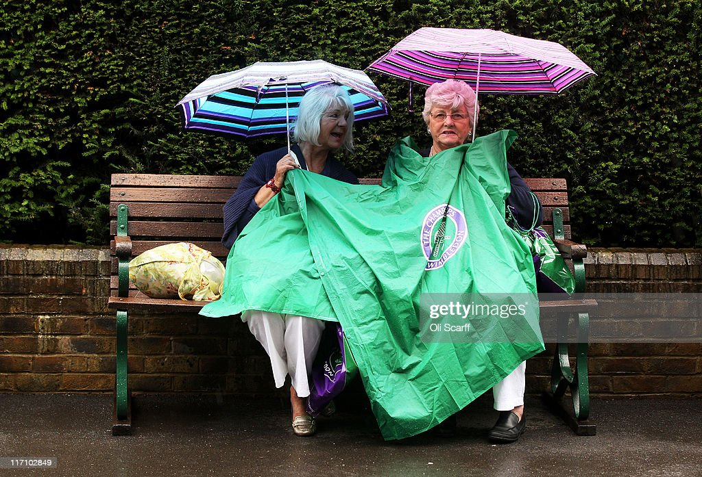 Tennis fans wait out rain delay on Day Three of the Wimbledon Lawn Tennis Championships at the All England Lawn Tennis and Croquet Club on June 22, 2011 in London, England.