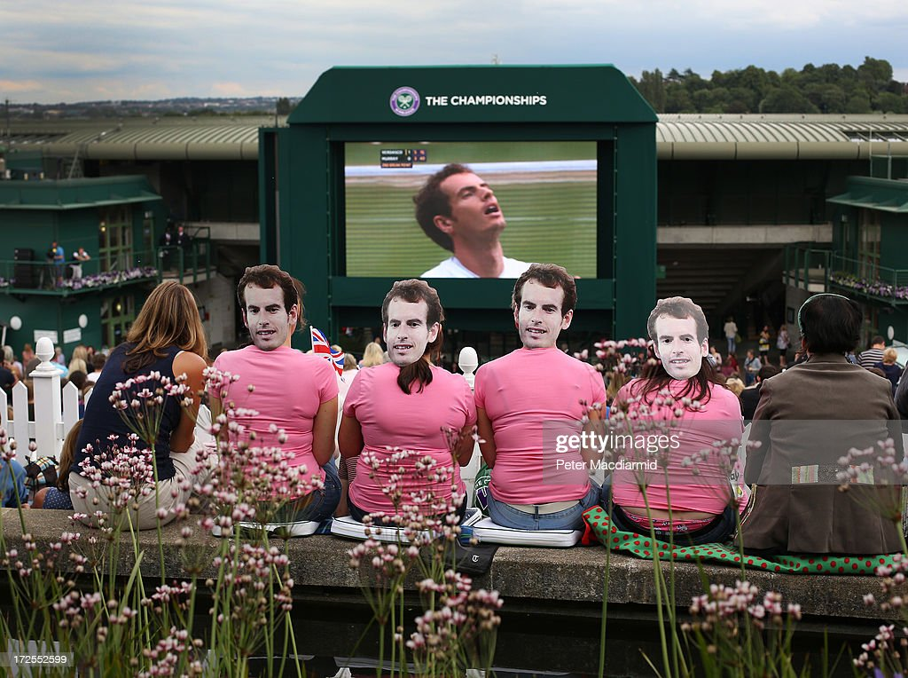 Tennis fans wearing masks depicting Britain's <a gi-track='captionPersonalityLinkClicked' href=/galleries/search?phrase=Andy+Murray+-+Tennisspelare&family=editorial&specificpeople=200668 ng-click='$event.stopPropagation()'>Andy Murray</a> watch a giant TV screen showing his match against Fernando Verdasco of Spain in their gentlemen's singles quarter final match on day nine of the Wimbledon Lawn Tennis Championships at the All England Lawn Tennis and Croquet Club at Wimbledon on July 3, 2013 in London, England.