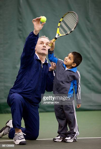 Tennis instructor works with five-year old student