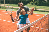 Cheerful father in sports clothing teaching his daughter to play tennis while both standing on tennis court
